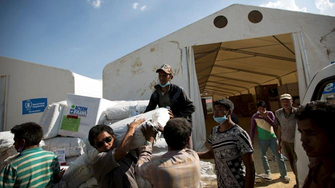 Workers load relief material onto a truck for earthquake victims at the cargo terminal of international airport in Kathmandu