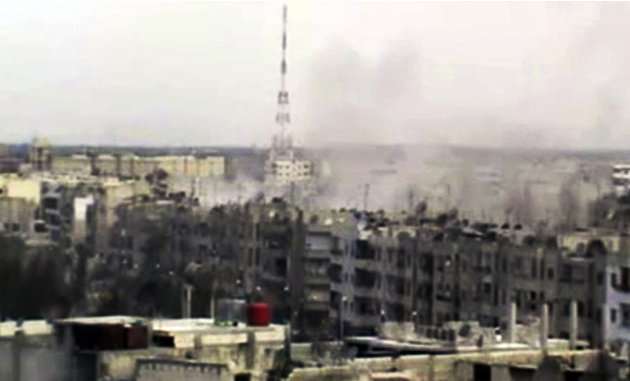 In this image made from amateur video released by the Shaam News Network and accessed Sunday, April 15, 2012, smoke rises from buildings across the city following purported shelling in Homs, Syria. Sy