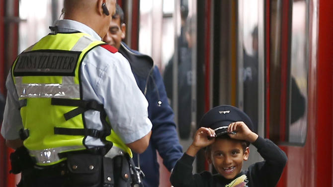 Migrant boy tries on Bahn security officer's cap after arriving by train from Salzberg at station in Munich