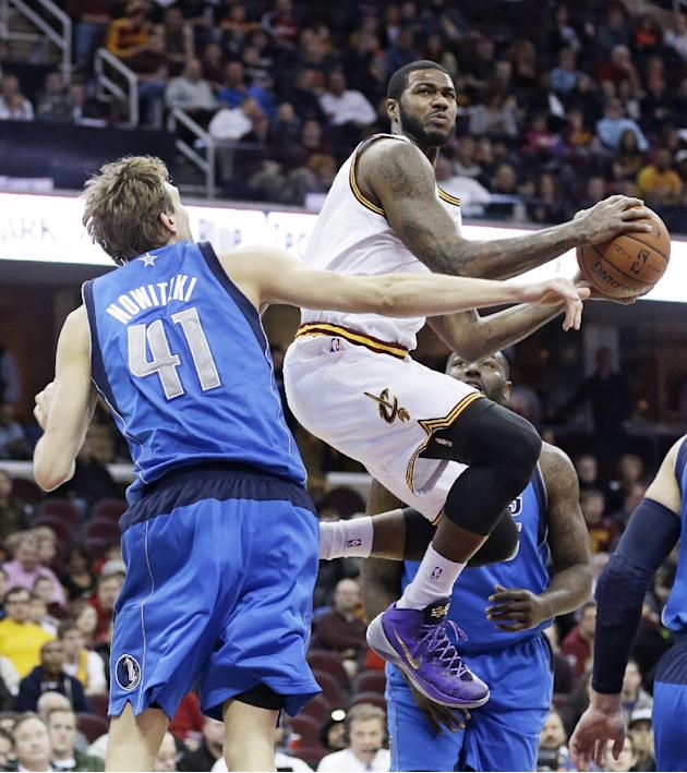 Cleveland Cavaliers' Earl Clark, center, jumps to the basket against Dallas Mavericks' Dirk Nowitzki (41), from Germany, during the first quarter of an NBA basketball game, Monday, Jan. 20, 20