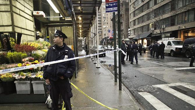 Police secure a sidewalk during the investigation of the scene where a man was fatally shot in the back of the head on Monday Dec. 10, 2012, in New York. Authorities said the man was shot outside a school near Columbus Circle in Manhattan, lying mortally wounded in a pool of blood as the suspect escaped with a getaway driver. (AP Photo/Bebeto Matthews)