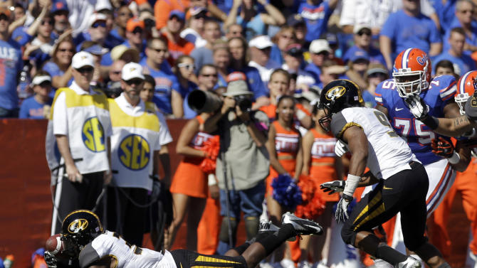 Missouri defensive back E.J. Gaines, left, recovers a fumble by Florida running back Mike Gillislee during the first half of an NCAA college football game  Saturday, Nov. 3, 2012, in Gainesville, Fla. (AP Photo/John Raoux)