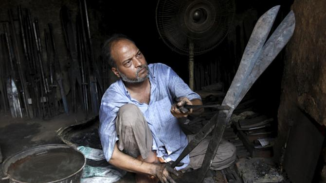 A blacksmith checks the blades alignment of a pair of scissors after shaping them at a workshop in Karachi