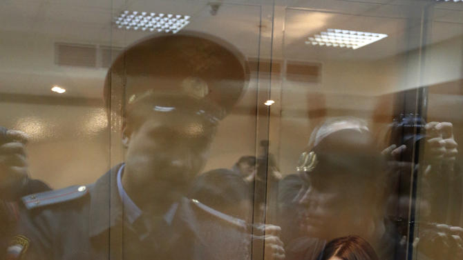 FILE - In this Monday Oct. 1, 2012 file photo, feminist punk group Pussy Riot members, from left, Maria Alekhina, Yekaterina Samutsevich and Nadezhda Tolokonnikova sit in a glass cage at a court room in Moscow, Russia. Lawyers for three members of the feminist punk group Pussy Riot are contesting their conviction in the European Court of Human Rights in Strasbourg. The complaint filed Wednesday, Feb. 6, 2013, alleges the group's conviction violates four articles of the European Convention on Human Rights guaranteeing freedom of speech, the right to liberty and security, the prohibition of torture, and the right to a fair trial.  (AP Photo/Sergey Ponomarev, file)