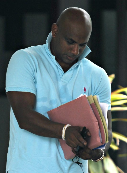 Chief selector Sanath Jayasuriya looks at his documents as he arrives at SLC board headquarters in Colombo