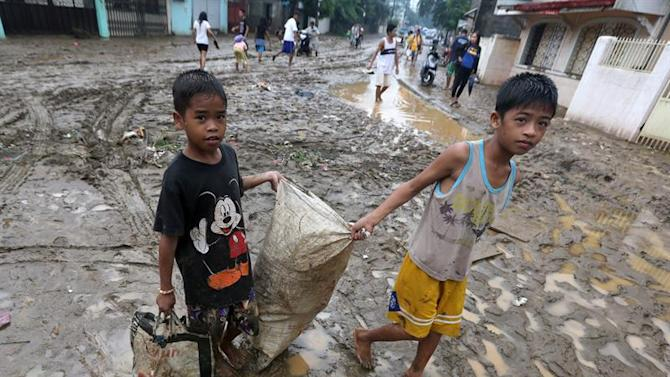 FRM12. Manila (Philippines), 19/09/2014.- Filipino flood victim children carry a sack of useful materials at a flood hit village in Marikina city, east of Manila, Philippines, 20 September 2014. At least four people were killed and tens of thousands of people fled their homes as Tropical Storm Fung-Wong triggered widespread floods in the Philippine capital and northern provinces, Office of Civil Defence said. Taiwan's Central Weather Bureau issued a warning for Tropical Storm Fung-Wong, saying it would bring heavy rain and strong winds when it makes landfall, the state-run Central News Agency reported. (Inundaciones) EFE/EPA/FRANCIS R. MALASIG