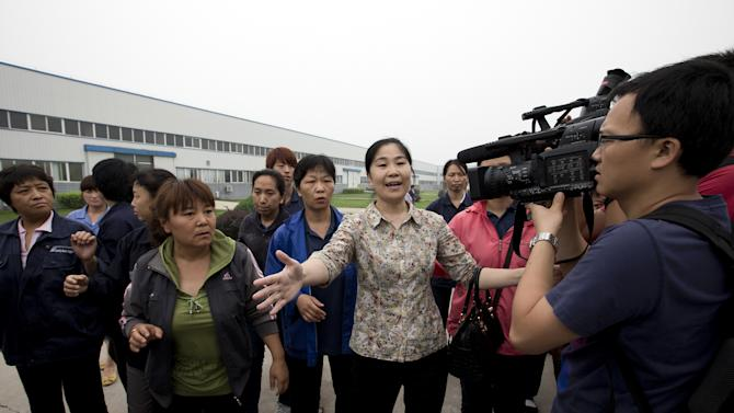 Chu Lixiang, director of workers union of Huairou District, center, and workers ask the journalists to leave from the Specialty Medical Supplies plant, where American Chip Starnes, a co-owner of the Florida-based plant, is being held hostage at the Jinyurui Science and Technology Park in Qiao Zi township of Huairou District, on the outskirts of Beijing, China Tuesday, June 25, 2013. (AP Photo/Andy Wong)
