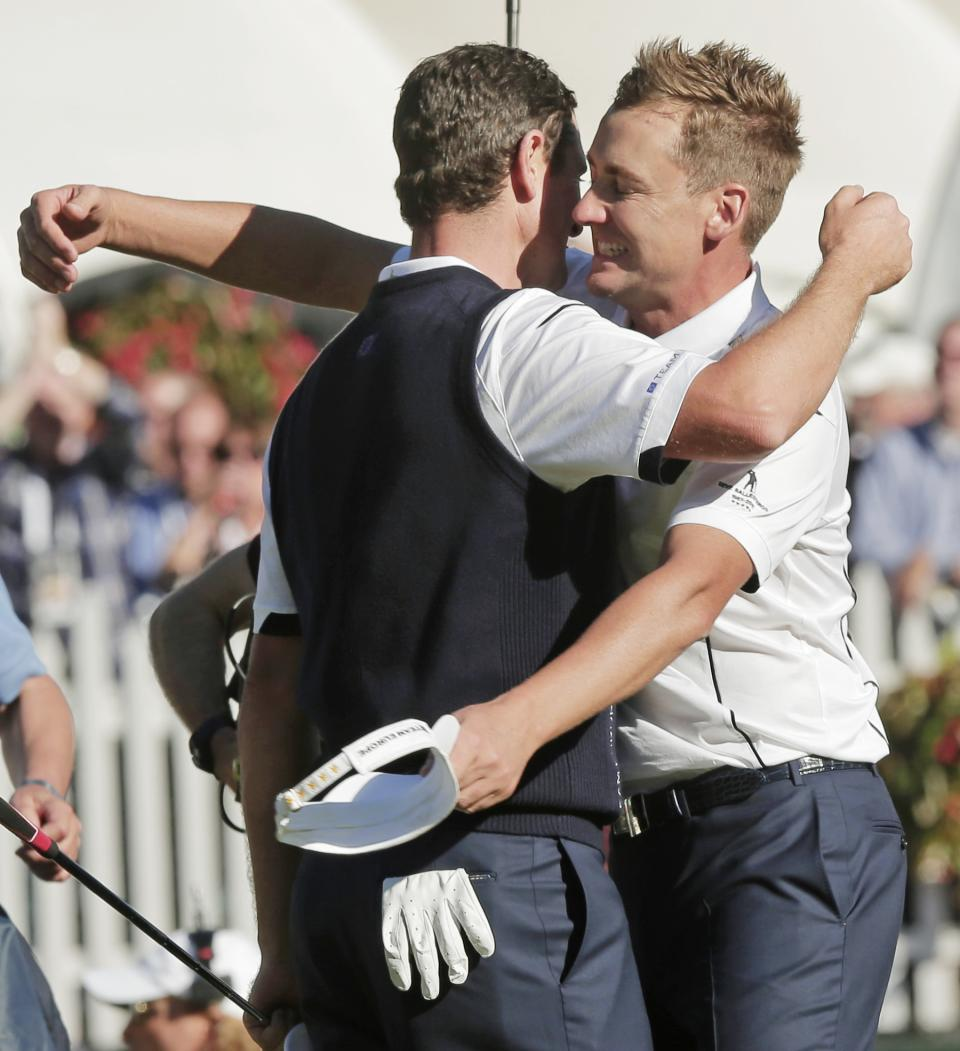 Europe's Ian Poulter, right, congratulates Justin Rose after Rose defeated USA's Phil Mickelson in a singles match at the Ryder Cup PGA golf tournament Sunday, Sept. 30, 2012, at the Medinah Country Club in Medinah, Ill. (AP Photo/Charlie Riedel)