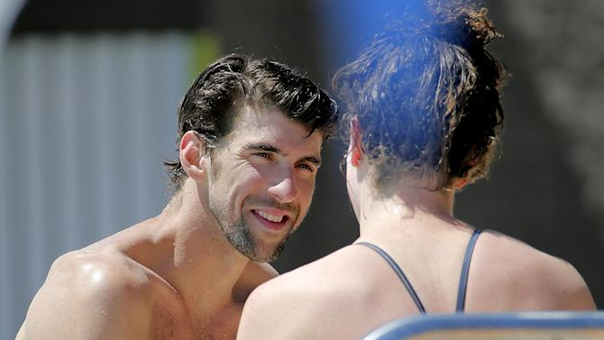 Michael Phelps talks with a fellow swimmer after practice, Wednesday, April 23, 2014, in Mesa, Ariz. Phelps is competing in the Arena Grand Prix at Mesa, as he returns to competitive swimming after a nearly two-year retirement. (AP Photo/Matt York)