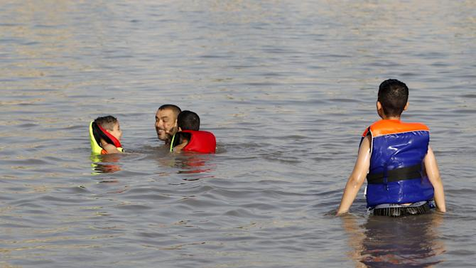 Residents swim in the Tigris river to cool off in northern Baghdad's Adhamiya district