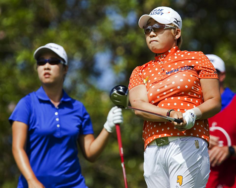 Haeji Kang, left, of South Korea, looks on as Jiyai Shin, right, of South Korea, watches her drive off the second tee in the third round of the LPGA LOTTE Championship golf tournament at Ko Olina Golf Club Friday, April 20, 2012, in Kapolei, Hawaii. (AP Photo/Eugene Tanner)