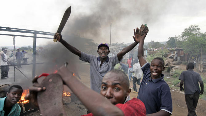 FILE - In this Jan. 28, 2008 file photo, Kenyan men from the Luo tribe armed with machetes and rocks enforce a makeshift roadblock, searching passing vehicles for Kikuyus trying to flee the town in order to kill them, during post-election violence on the main road to the Ugandan border near the airport in Kisumu, Kenya. The toll of more than 1,000 dead after Kenya's last election makes the presidential vote on Monday, March 4, 2013 the most important in the country's 50-year history, while a slate of new races and a presidential candidate Uhuru Kenyatta who faces charges at the International Criminal Court also make it Kenya's most complicated. (AP Photo/Ben Curtis, File)
