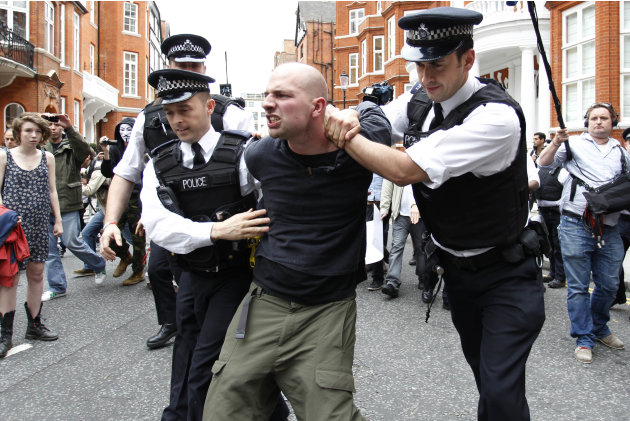 British police officers arrest a protesters in support of WikiLeaks founder Julian Assange from the front of Ecuadorian Embassy in central London, London, Thursday, Aug. 16, 2012. WikiLeaks founder Ju