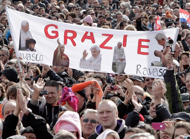 "Faithful hold up a banner with pictures of Pope Benedict XVI and writing reading in Italian ""Thank you"" as they attend Benedict's last Angelus prayer, in St. Peter's Square, at the Vatican, Sunday, Fe"