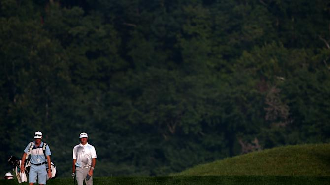 Bubba Watson of the United States walks up a hole with caddie Ted Scott prior to the start of the 96th PGA Championship at Valhalla Golf Club on August 5, 2014 in Louisville, Kentucky