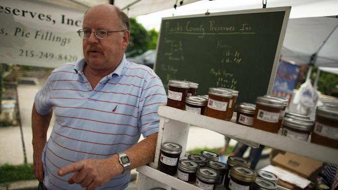 Jerry Krone, owner of Bucks County Preserves, talks with a customer at the farmers market, Saturday Oct. 6, 2012, in Doylestown Pa.  When the recession cost Jerry Krone his longtime accounting job several years ago, he turned to his hobby, making gourmet jam in his Fountainville kitchen. Krone says neither President Barack Obama nor Mitt Romney truly understands what average families are going through. A registered Republican, Krone voted for Obama in 2008. (AP Photo/ Joseph Kaczmarek)