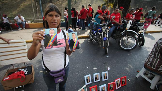 A street vendor shows off her images for sale of Venezuela's President Hugo Chavez at an event commemorating the 1958 fall of the country's last dictatorship in Caracas, Venezuela, Wednesday, Jan. 23, 2013. Chavez, who was re-elected to another six-year term in October, has not appeared or spoken publicly since he left for Havana on Dec. 10. Government officials have said the 58-year-old president is improving after suffering complications including a severe respiratory infection, but they have not provided specific details about his health. (AP Photo/Fernando Llano)