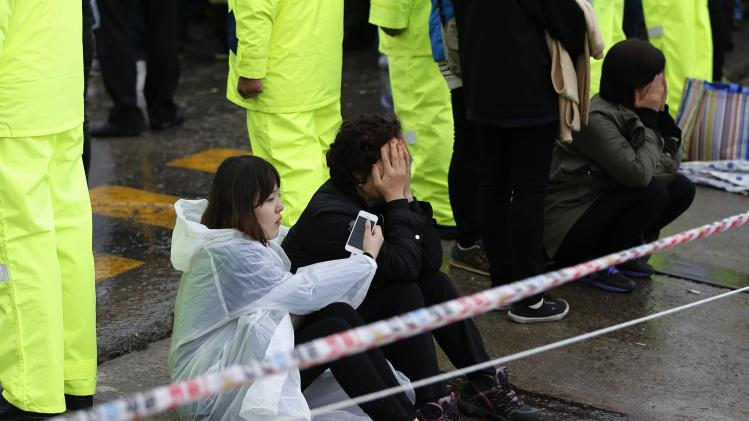 "Family members of missing passengers who were on South Korean ferry ""Sewol"", which sank in sea off Jindo, cry as they look towards the port where others have gathered, in Jindo"