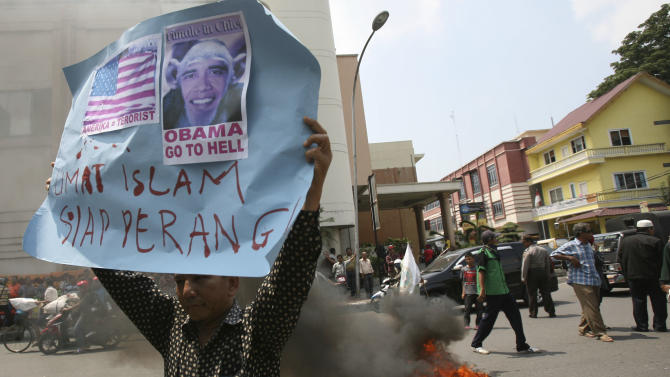 """An Indonesian Muslim holds up a poster as a tire burns during a protest against an American film that ridicules Prophet Muhammad outside the U.S. Consulate in Medan, North Sumatra, Indonesia, Tuesday, Sept. 18, 2012. Indonesians continue to protest the anti-Islam film """"Innocence of Muslims,"""" torching the flag and tires outside the consulate in the country's third largest city of Medan. The poster reads: """"Muslims are ready for war.""""(AP Photo/Binsar Bakkara)"""