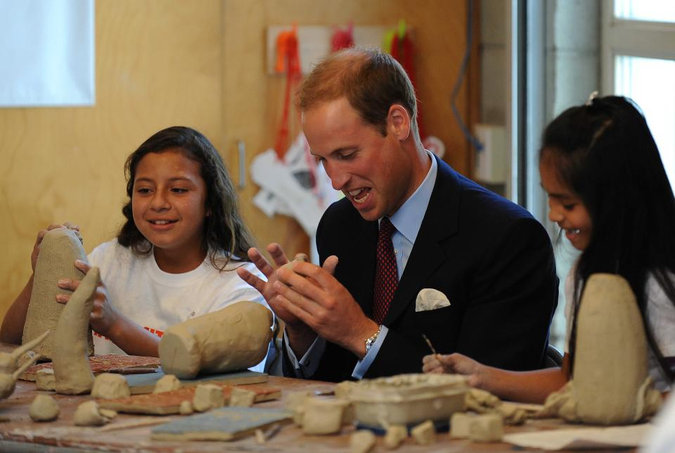 Prince William, the Duke of Cambridge, plays with clay with students in a ceramics class during a tour of the Inner City Arts academy in Los Angeles, Sunday, July 10, 2011. (AP Photo/Mike Nelson, Pool)