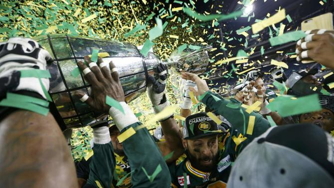 Edmonton Eskimos quarterback Mike Reilly is surrounded by his teammates as they raise the Grey Cup after his team defeated the Ottawa Redblacks in the CFL's 103rd Grey Cup championship football game in Winnipeg