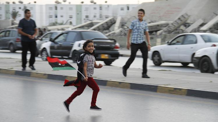 In this Tuesday, Oct. 23, 2012 photo, a Libyan girl runs on the street in front of the destroyed remnants of deposed dictator Moammar Gadhafi's compound Bab al-Aziziya in Tripoli, Libya. One year on the country is still trying to overcome the legacy of one of the most erratic leaders of modern times as well as a brutal eight month struggle that left the country awash in weapons, militias and very few viable institutions of the state.(AP/Paul Schemm)