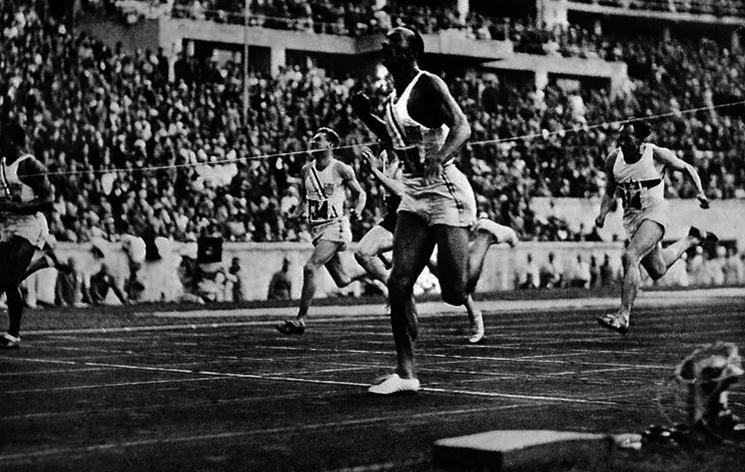 Jesse Owens wins the 100-meter dash in the 1936 Olympics — Agence French Press