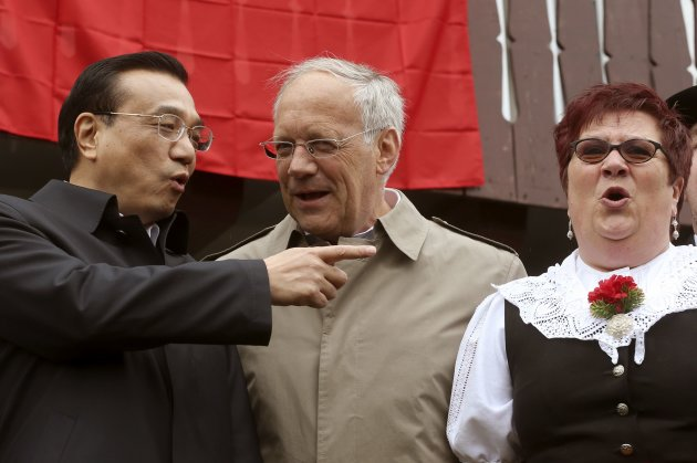 Chinese Premier Li Keqiang talks to Swiss Economy Minister Schneider-Ammann as a member of the Jodelclub Saengerrunde Zurich yodel band performs during their visit to Guldenberg farm in Embrach