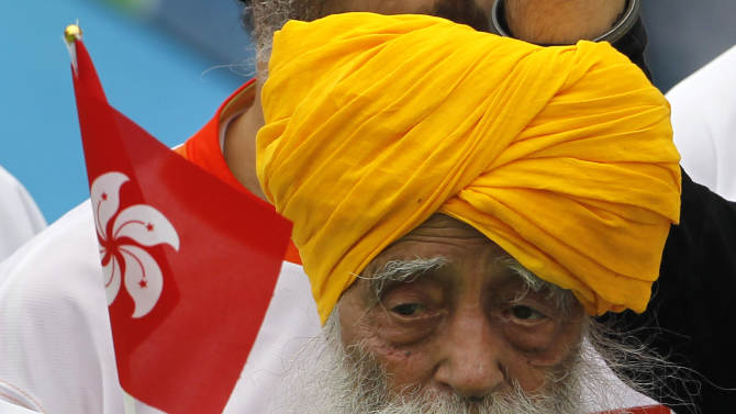 Centenarian marathon runner Fauja Singh, 101, center, originally from Beas Pind, in Jalandhar, India but who now lives in London, raises a Hong Kong flag after finishing a 10-kilometer race, which was part of the annual Hong Kong Marathon, in Hong Kong Sunday, Feb. 24, 2013. Singh will retire from public racing after competing in the marathon. (AP Photo/Vincent Yu)