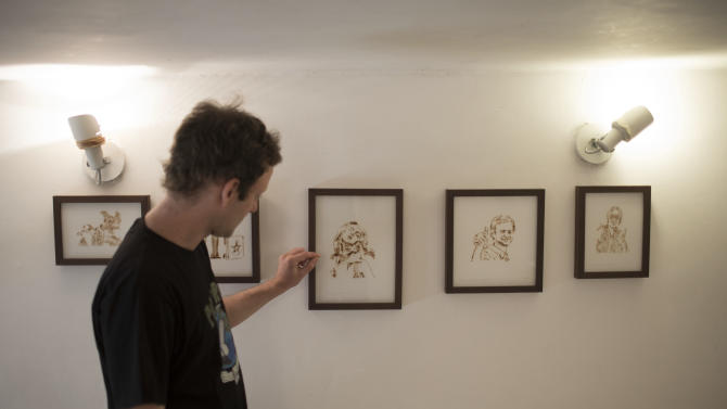 Brazilian artist Fernando de la Rocque stands in front of some of their pieces of art at the La Cucharacha, a small alternative gallery in the stylish, in Rio de Janeiro, Brazil, Monday Aug.  20, 2012. Some of Rocque's pot-stained prints are being sold for $2,500 each. It takes him a week to complete a single print blowing about five joints' worth of smoke onto a paper daily.  (AP Photo/Felipe Dana)