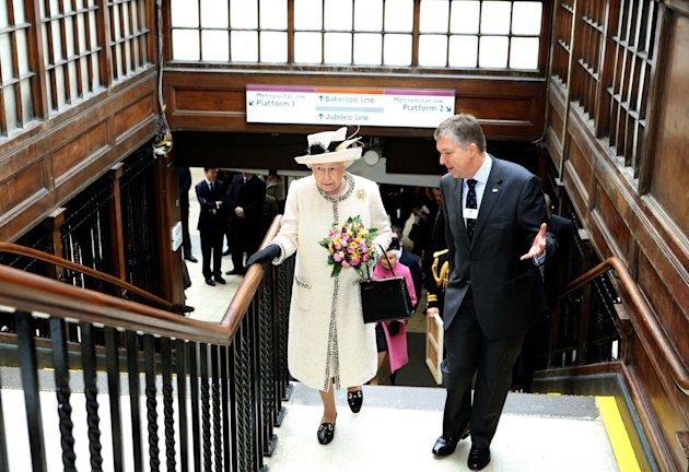 Britain's Queen Elizabeth speaks with the managing director of London Underground during her visit to Baker Street underground station in London