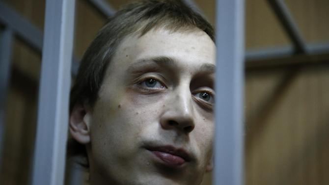 Pavel Dmitrichenko looks through bars as he stands in a cage at a court room in Moscow on Tuesday, Oct. 22, 2013. Bolshoi dancer Dmitrichenko goes on trial on Tuesday, on charges of organizing an acid attack against the ballet's artistic director, Sergei Filin. (AP Photo/Alexander Zemlianichenko)