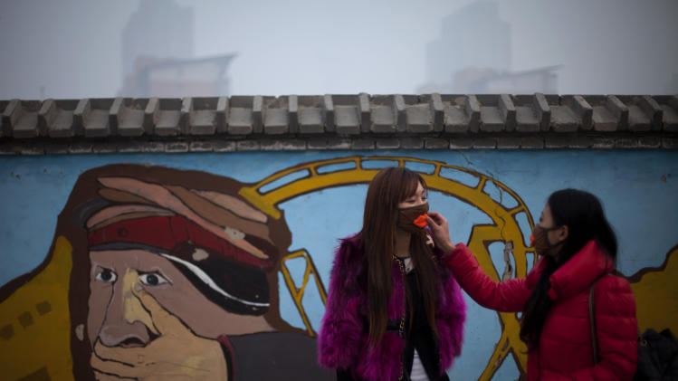 A woman helps adjust a mask for her friend outside an amusement park on a hazy day in Beijing Saturday, Jan. 12, 2013. Air pollution levels in China's notoriously dirty capital were at dangerous levels Saturday, with cloudy skies blocking out visibility and warnings issued for people to remain indoors. (AP Photo/Alexander F. Yuan)