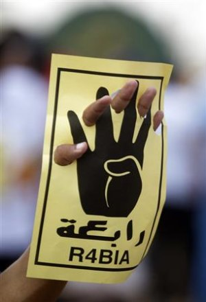 A member of the Muslim Brotherhood holds up a sign…