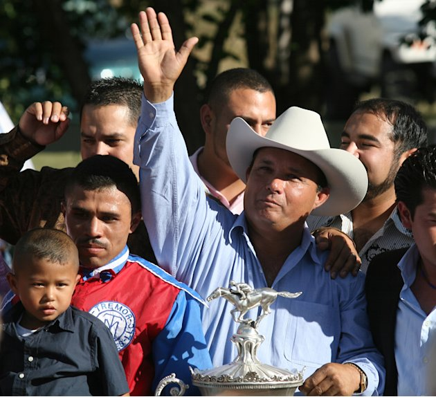 In this photo taken Sept. 6, 2010, owner Jose Trevino Morales, center, acknowledges the crowd as he stood with the trophy after Mr. Piloto won the All American Futurity horse race at Ruidoso Downs, N.