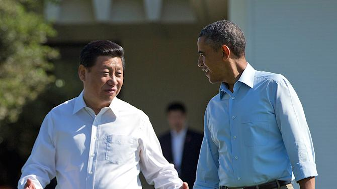 """President Barack Obama and Chinese President Xi Jinping, left, walk at the Annenberg Retreat of the Sunnylands estate Saturday, June 8, 2013, in Rancho Mirage, Calif. Obama told reporters his meetings with Xi have been """"terrific,"""" while saying it is critical that the U.S. and China reach a """"firm understanding"""" on cyber issues. (AP Photo/Evan Vucci)"""
