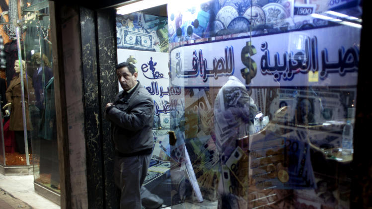 "A man leaves after changing foreign currency at a currency exchange office, in Cairo, Sunday, Jan. 6, 2013. The Arabic on the window reads: ""Arabian Egypt for Exchange.""  Egypt swore in 10 new ministers on Sunday in a Cabinet shake-up aimed at improving the government's handling of the country's ailing economy ahead of talks this week with the International Monetary Fund over a badly needed $4.8 billion loan. (AP Photo/Nasser Nasser)"