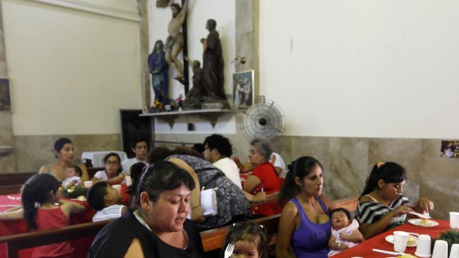 Impoverished people share a Christmas meal distributed to them at the parish church San Pedro de La Boca in Buenos Aires