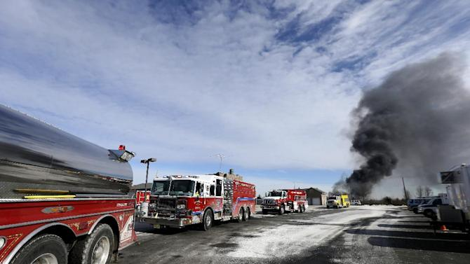 Fire trucks wait in line to fill up on water to battle a large warehouse fire a day after flames engulfed the facility, Friday, Feb. 12, 2016, in Hillsborough, N.J. Firefighters have contained the massive  fire and officials said the blaze didn't pose an imminent public health threat. Fire officials say plastic pellets were being stored in most of the complex, and environmental officials have been testing air quality. (AP Photo/Julio Cortez)
