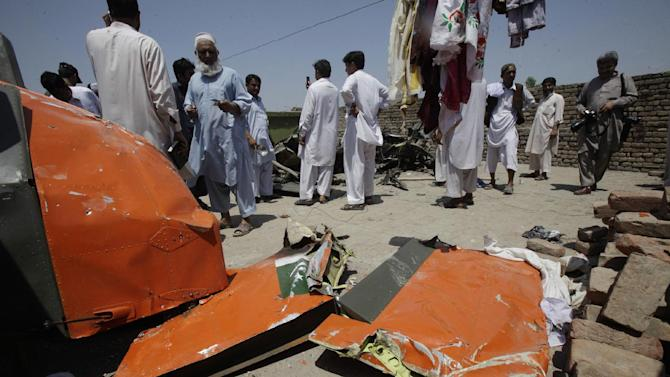 People on a rooftop look at a wreckage of a plane which crashed in Nowshera, 45 kilometers (21 miles) east of Peshawar, Pakistan Thursday, May 17, 2012. Two Pakistani air force planes crashed in a residential area in northwestern Pakistan on Thursday, killing all four pilots on board and injuring five people on the ground, police said. (AP Photo/Mohammad Sajjad)