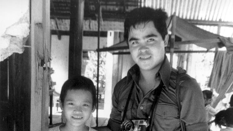 FILE - In this 1973 file photo, Phan Thi Kim Phuc, left, is visited by Associated Press photographer Nick Ut at her home in Trang Bang, Vietnam. As a nine-year-old, Kim Phuc was the subject of a Pulitzer Prize-winning photo by Ut as she fled in pain from a misdirected napalm attack against her village by South Vietnamese planes in 1972.  After taking the photograph, Ut came to the girl's aid and transported her to a hospital. (AP Photo/File)