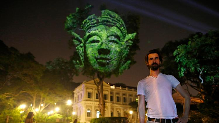 "French artist Briend poses with his photographic light installation ""Divine Trees"" during a media preview of the Singapore Night Festival in Singapore"