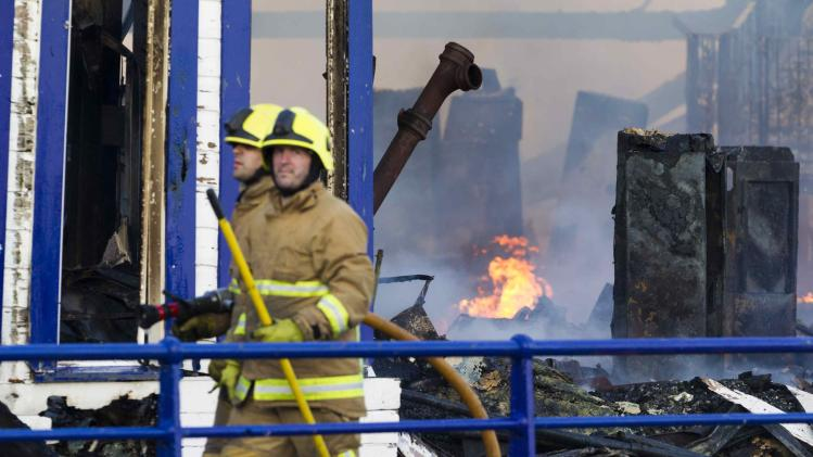 Fire fighters from the East Sussex Fire and Rescue Service are pictured as they work to dampen down flames following a fire on the pier in Eastbourne