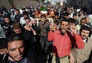 Syrian mourners shout slogans as they carry the body of Mohammed Hafar, 20, during his funeral in the northern Syrian town of Azaz. Explosions shook Damascus as warplanes launched their heaviest air raids yet and two car bombs struck on Monday, with the UN-Arab League peace envoy saying Syria's conflict was going from bad to worse
