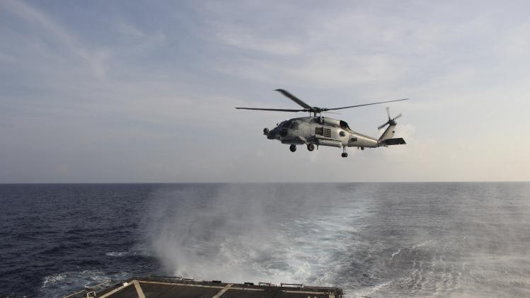 Handout picture of A U.S. Navy SH-60R Seahawk helicopter takes off from the destroyer USS Pinckney in the Gulf of Thailand, to assist in the search for missing Malaysian Airlines flight MH370