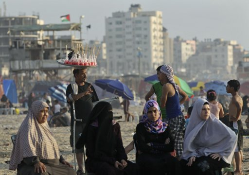 Palestinians sit on a beach in Gaza City