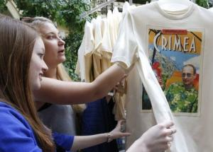 Women inspect T-shirts, displaying images of Russia's President Vladimir Putin, which are on sale at GUM department store in central Moscow