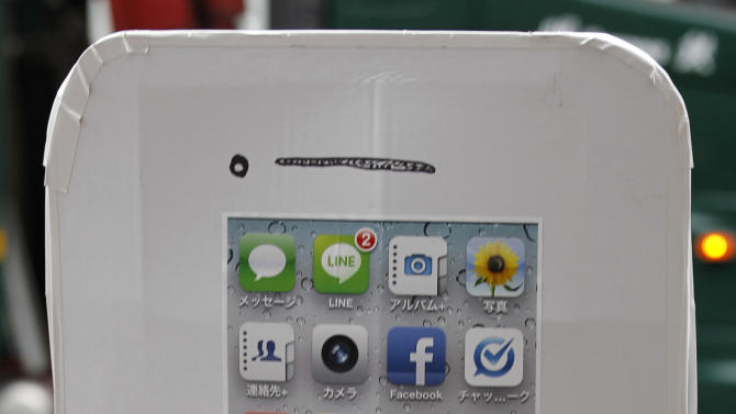 Daichi Tanaka, 31, waits in line to buy Apple's iPhone 5 outside a store in Tokyo Friday morning, Sept. 21, 2012. (AP Photo/Koji Sasahara)