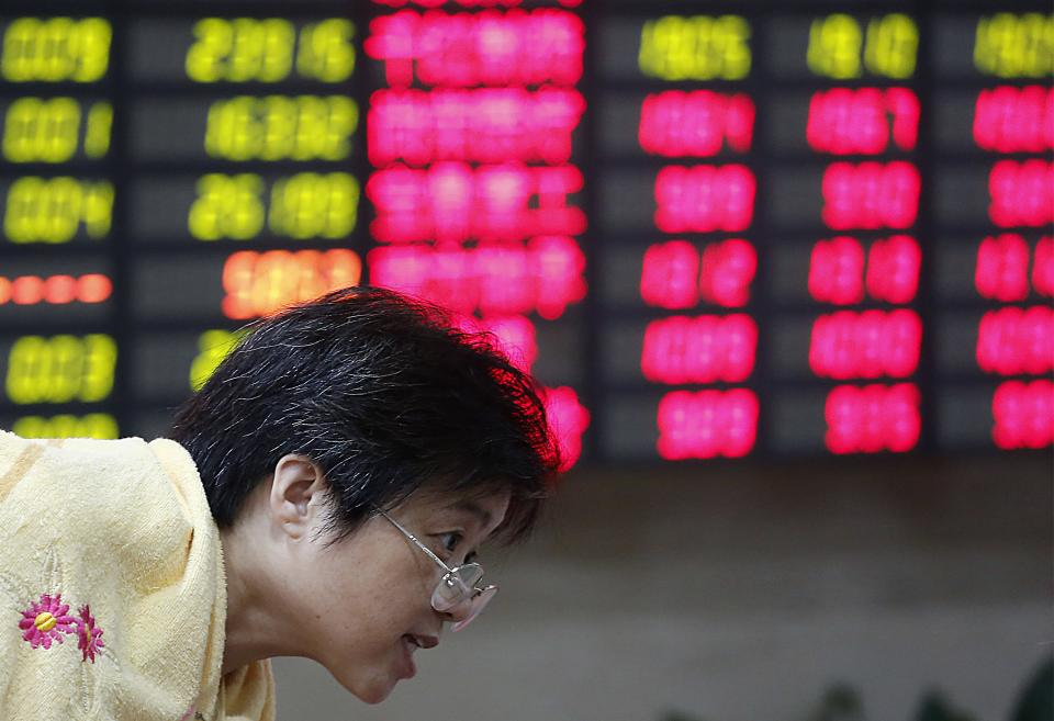 An investor looks at a stock price monitor at a private securities company Tuesday, Sept. 4, 2012, in Shanghai, China. Asian stock markets fell Tuesday as uncertainty persisted about what authorities in the U.S., China and Europe might do to deal with a souring global economy. (AP Photo)
