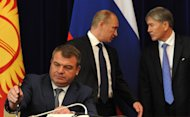 Then-Russian defence minister Anatoly Serdyukov (left) signs a document as President Vladimir Putin (centre) and his Kyrgyz counterpart Almazbek Atambayev (right) speak at Atambayev&#39;s residence near Bishkek on September 20, 2012. Russian investigators said Friday they may press charges against Serdyukov after he refused to answer questions about his alleged role in an illegal property scheme